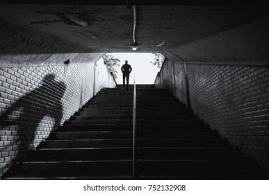 Man walking up the stairs of an old tunnel in the city. Crime concept.
