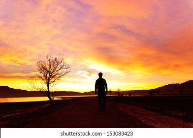 Man walking at sunset on the mountain lake in a majestic summer sunset