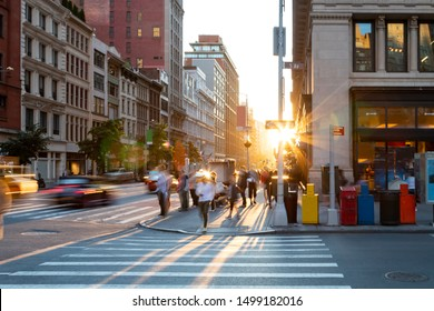 Man walking through the crosswalk at the busy intersection of 5th Avenue and 23rd Street in New York City with bright light of sunset in the background