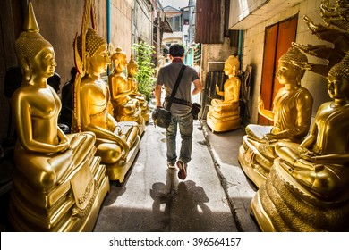 Man was walking through golden buddha road.Bangkok Thailand.