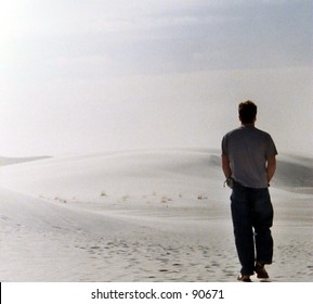 Man walking through White Sands, New Mexico.