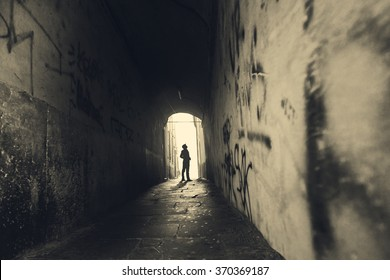 Man walking in a tight tunnel in the city