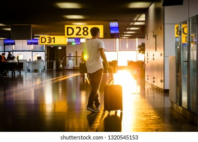 Man walking towards airport gate with roller suitcase at sunrise