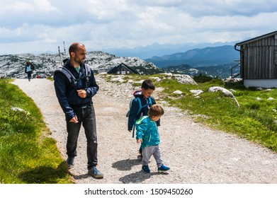 Man walking with two young boys on a footpath along green grass on a Alp mountain during a trip in Dachstein on circa July 2019 in Obertraun, Austria.