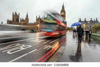 A man walking in an umbrella on a rainy London day
