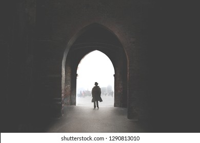 man walking under arch discovering the city