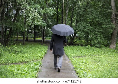 The man is walking under a black umbrella