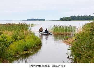 A man walking in the water is leading a dinghy with a woman sitting in it for fishing in a lake