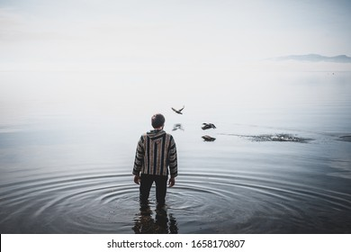 Man walking in the water sea lake ocean birds ducks flying on the water human with ethnical dress obscurity and moody shot