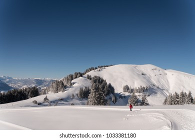 Man walking in winter landscape in the Swiss Alps on a sunny day with blue skied and lots of fresh snow and snow covered mountain peaks and lot of trees and forest