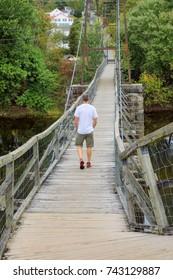 Man walks across the scary, creaky, historic Buchanan Swinging Bridge that crosses over the James River in Virginia.