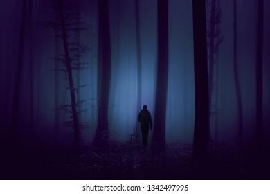 Man walks alone in dark mystical violet colored foggy forest.