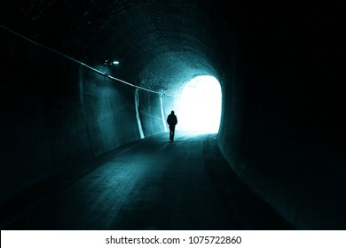 Man walks alone in the dark tunnel with light at the end.