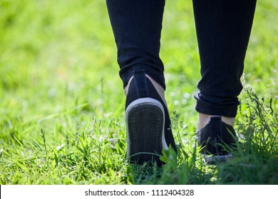 Man walks along grass in rubber sneakers and black pants, close-up view from behind