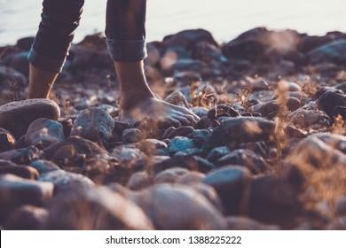 man walks barefoot on the beach of stones on the seashore