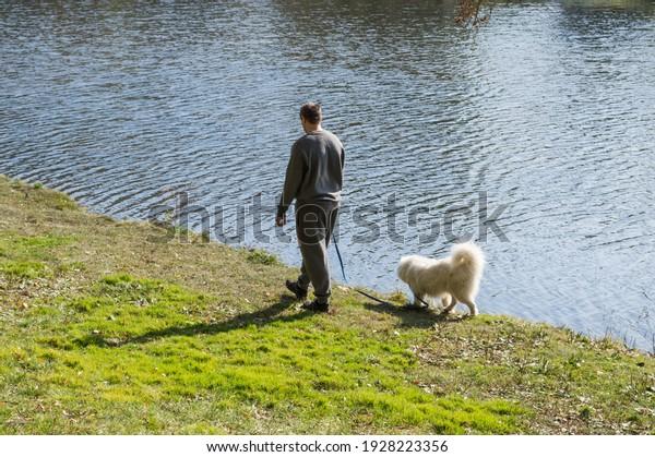 man-walks-his-dog-along-600w-1928223356.