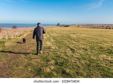 A man walks his dog heading to Reculver Towers,  Reculver, Kent, UK along the cliff top walk on the coastal path near to Herne Bay and Whitstable.