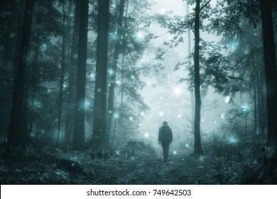 Man walks in magical dark turquoise colored foggy wild forest with abstract firefly bokeh lights.