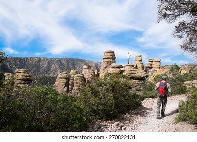A man walks on the trail, the child climbed up on a rock and waiting for his father. Echo Canyon Trail. Chiricahua National Monument, Arizona, United States