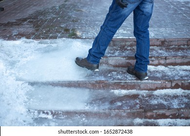 a man walks up stairs with ice steps, poor work of public utilities