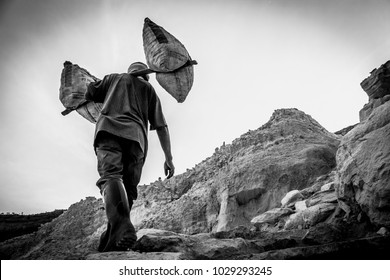 Man walks up to the top of the volcano carrying heavy bags of sulfur on his shoulder.