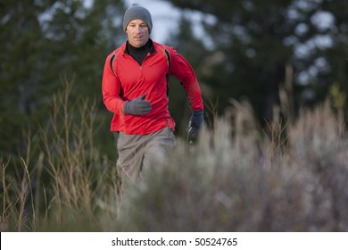 A man walks toward the camera through a brush-filled clearing. He is looking downward and wearing a hat, gloves, and activewear. Horizontal format.