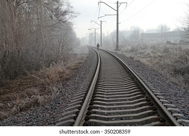 A man walks in the winter by rail in the fog.