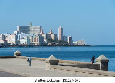 Man in the wall of the Malecon with the modern city in the background, a very popular place in Havana where the population rests among many other activities. Havana. Cuba January 2, 2109