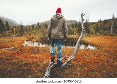Man wanderer standing alone in swamp forest travel lifestyle concept adventure vacations scandinavian woods nature