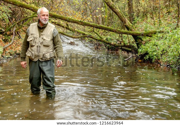 A man wanders through the autumnally colored Neckar valley and stands with his waders up to his knees in the water of the river Neckar, which is still a narrow stream near its source.