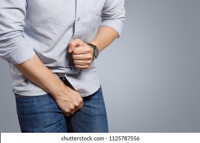 Man wanting to the toilet and holding his groin on grey background