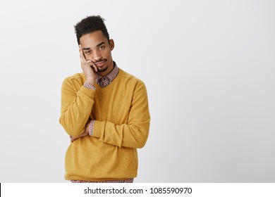 Man wants to be somewhere else. Bothered attractive young man with afro hairstyle leaning head on palm, feeling bored and indifferent, expressing desire to leave and annoyance over gray wall