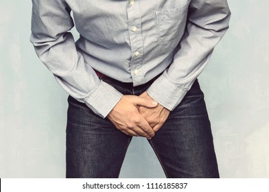 Man wants to pee and is holding his bladder. Incontinence. Disease for men. Men's health. The pain from the blow in groin.