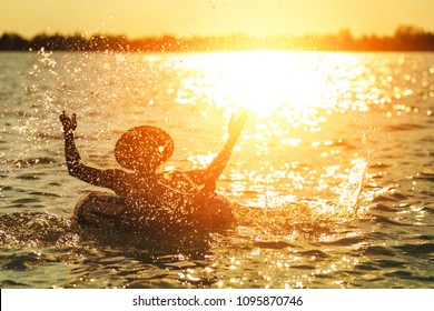 A man ware hat and he is on swim tube in the water. He is hands up to make water splash.