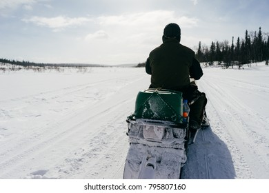 a man in warm clothes is riding on a snow-covered field
