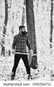 Man with warm gloves and checkered jacket in forest. Macho with beard and mustache holds ax. Guy with strict face with trees covered by snow on background. Hipster woodsman concept.