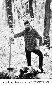 Man with warm gloves in forest. Macho with beard and mustache poses with yellow ax. Woodsman with smiling face holds axe near trees covered with snow on background. Fashionable woodsman concept.