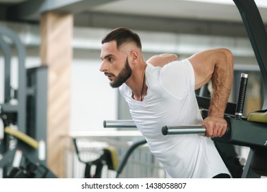 Man warm up in the gym. Handsome bearded man trains