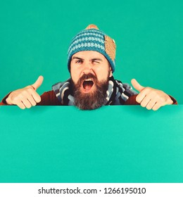Man in warm hat shows thumbs up on green background, copy space. October and November sale idea. Autumn and cold weather concept. Hipster with beard and flirty face wears warm clothes