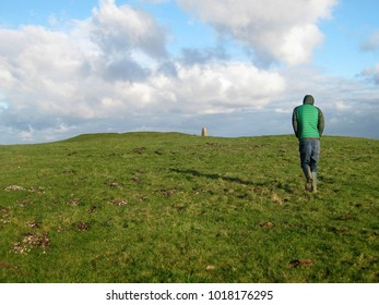 Man in warm jacket and wellies walking purposefully towards small monument on summit of hill, focus concept