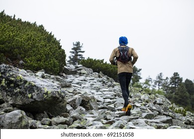 man in warm sportswear and with backpack running up the hill on mountain track in cold rain