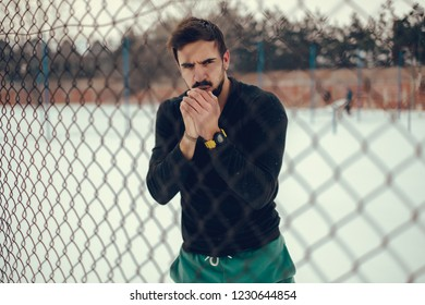 Man warming hands with his breath behind the fence on a cold winter day