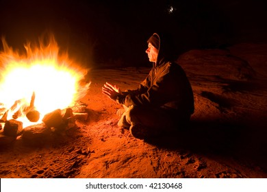 Man warming himself in front of blazing campfire on a cold night of camping. Full moon showing through tree branches in background.