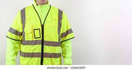 A man with warning safety clothes for roadworks and construction sites. High visibility reflective yellow safety vest. Plenty of copy space for your own text.