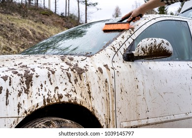 Man washes away the dirt with a brush with a dirty car in the countryside