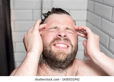 Man washes away the shampoo from the hair and the foam got into his eyes causing unpleasant painful sensations. Close-up.