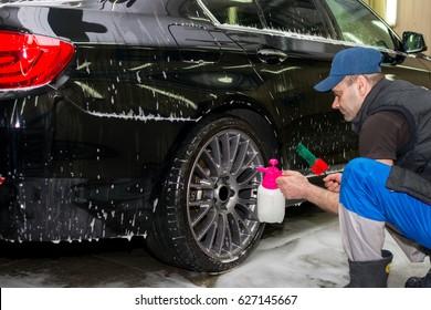 A man washes a black car with foam
