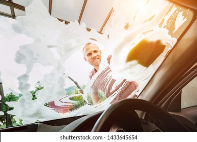 Man washes car front windows with soap foam