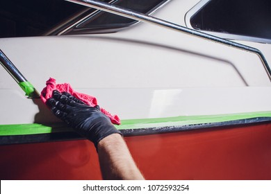 Man washes deck yacht with pink rag. preparation in polishing, repair yacht, boat