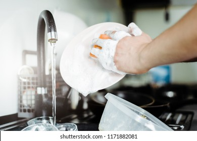 The man washes the dirty dishes by hand with dish soap. Dirty dishes in the sink. No dishwasher. Concept of caring for dishes in the kitchen. The kitchen sink is full of dirty dishes.